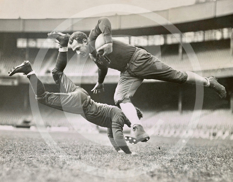 Chicago Bears teammates practicing as Joe Zeller tries to tackle Red Grange. 18 March 1935.