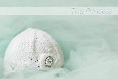 The Princess knit beanie has a scalloped edge and a rhinestone button.