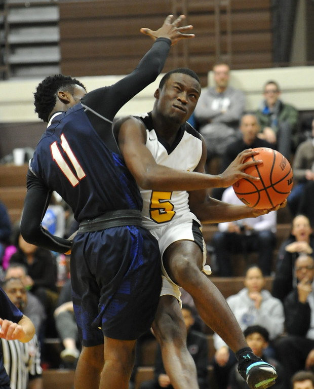 . Ferndale\'s Reggie Davis (5) drives to the basket as Berkley\'s TJ McGibbon defends  during the OAA Blue match up played on Thursday January 11, 2018 at Ferndale HS.  The Eagles lost to the Bears 54-49.  (Oakland Press photo by Ken Swart)
