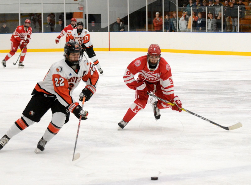 Birmingham Brother Rice senior Alec DeLuca skates up ice as Orchard Lake St. Mary's junior Ryan Tucker closesin. Th Warriors opened up their home season with a 5-2 victory over Orchard Lake St. Mary's Wednesday night at the Oak Park Ice Arena. (MIPrepZone photo by Jason Schmitt)