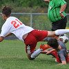 Lutheran High Northwest's Colin Jones (21) is tripped up by Clarenceville's Nicholas Snage during the match played on Wednesday September 7, 2016 at LHNW.  The Crusaders lost to the Trojans 1-0. (MIPrepZone photo by Ken Swart)