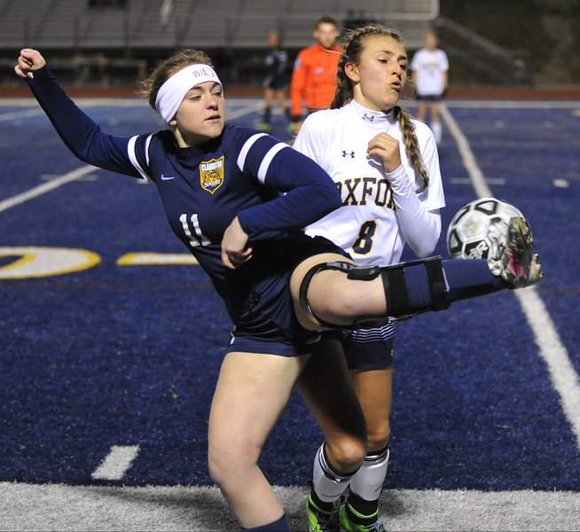 Clarkston's Maddy Dooling (11) gets a leg up on Oxford's Anne Culver (8) during the match played on Tuesday April 11, 2017 at Oxford HS.  The Wildcats and Wolves played to a 1-1 draw.  (MIPrepZone photo by Ken Swart)