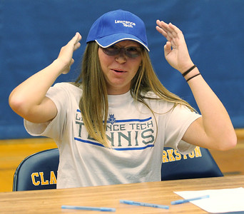 Samantha Weber tries on a Lawrence Tech hat for size during national signing day ceremonies at Clarkston High School Wednesday, Nov. 8, 2017. Weber will take her tennis skills to Tech next season after signing a National Letter of Intent. (For The Oakland Press / LARRY McKEE)
