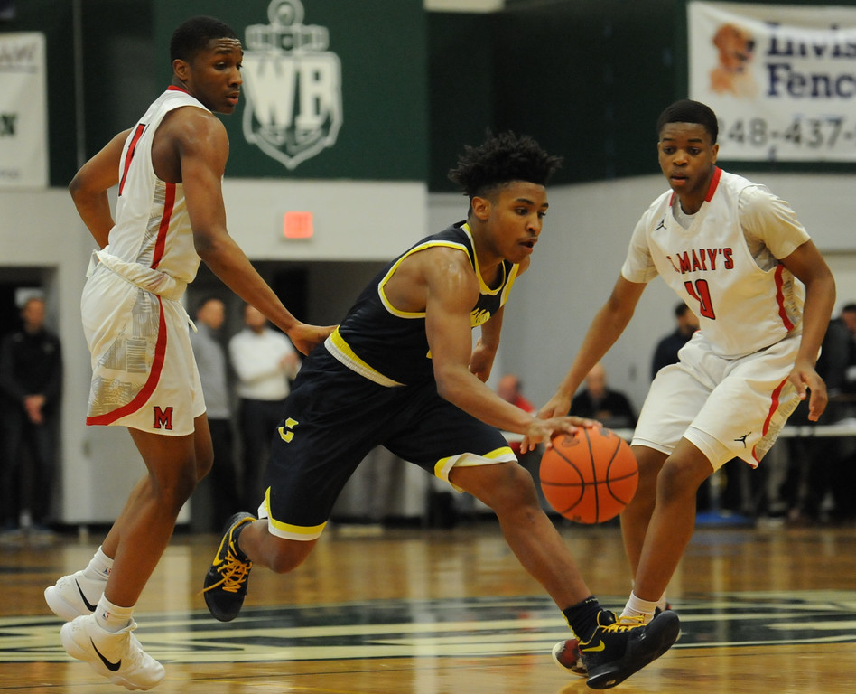 . Clarkson\'s CJ Robinson (3) splits the defense of Orchard Lake St Mary\'s Lorne Bowman (L) and Chizi Nwaopara (R) during the Class A Regional Final held on Wednesday March 14, 2018 at West Bloomfield HS.  The Wolves defeated the Eaglets 58-35.  (Oakland Press photo by Ken Swart)