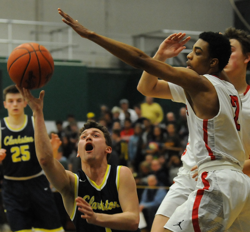 . Clarkson\'s Foster Loyer puts up an off balance shot as Orchard Lake St Mary\'s Geordon Duncan defends during the Class A Regional Final held on Wednesday March 14, 2018 at West Bloomfield HS.  Loyer had a game high 24 points to help lead the Wolves to a 58-35 win.  (Oakland Press photo by Ken Swart)