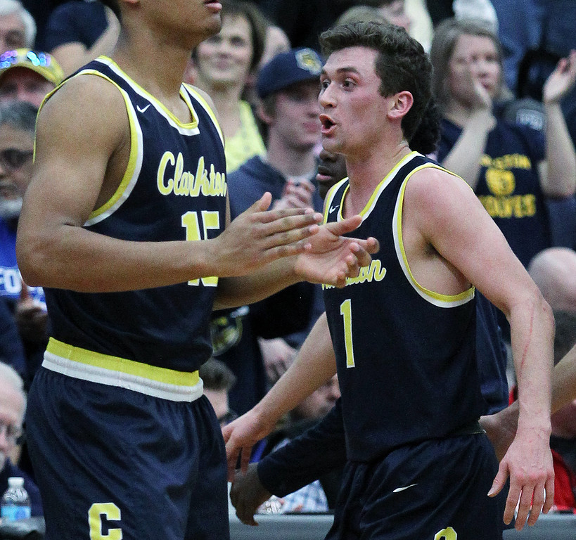 . Foster Loyer (1), Clarkston, celebrates on the sidelines during Class A quarterfinal basketball action against Flint Carman-Ainsworth at Grand Blanc High School Tuesday, March 20, 2018. The Wolves, led by Loyer\'s game high 19-points, downed the Cavaliers 52-31 and will now move on to Lansing for the state finals this weekend. (For The Oakland Press / LARRY McKEE)