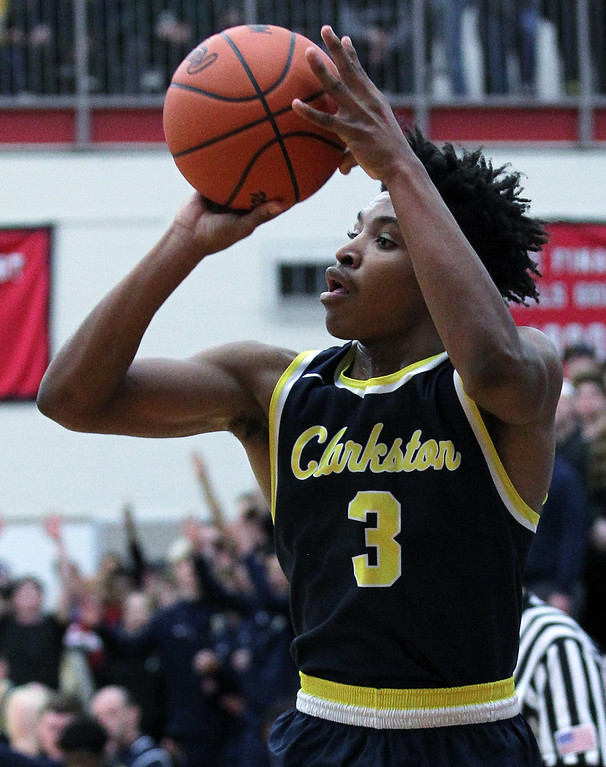 . C.J. Robinson, Clarkston, goes up goes up for a three during Class A quarterfinal basketball action at Grand Blanc High School Tuesday, March 20, 2018. Robinson scored 12-points to help Clarkston defeat the Cavaliers 52-31. (For The Oakland Press / LARRY McKEE)
