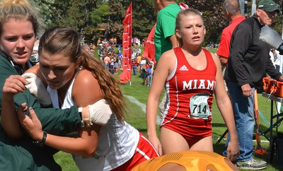Miami's Jackie Mullins (714) searches for her teammates while an MSU helper assists a runner.