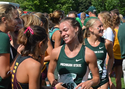 MSU's Aubrey Wilberding shares a chat with a Birmingham Seaholm runner.