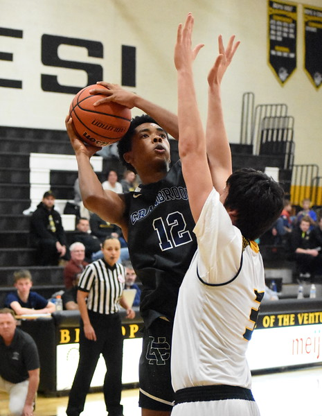 Bloomfield Hills Cranbrook-Kingswood's Jordan Benson goes up for a shot as Bishop Foley's Mike Maten defends during the second half of the Cranes' 67-57 win over the Ventures Friday night. (Digital First Media photo by Jason Schmitt)