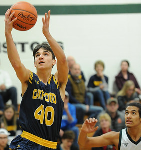 Oxford's Michael Raisch (40) drives past Farmington Hills Harrison's Max Martin for two of his team high 17 points during the OAA Blue match up played on Friday January 4, 2019 at Harrison HS.  The Wildcats won the game 79-48.  (Digital First Media photo by KEN SWART)
