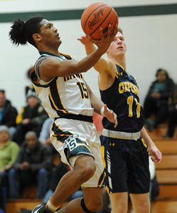 Farmington Hills Harrison's Trenton Ramsey (15) lays in two of his 11 points as Oxford's Grant Kornburger (11) defends during the OAA Blue match up played on Friday January 4, 2019 at Harrison HS.  The Hawks lost to the Wildcats 79-48.  (Digital First Media photo by KEN SWART)
