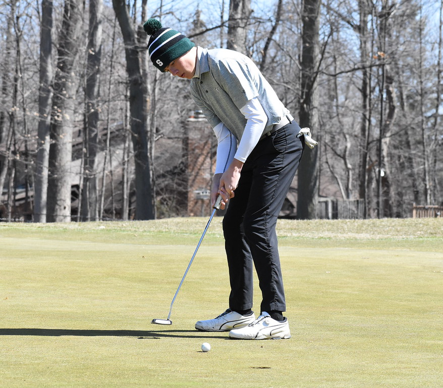 . Birmingham Seaholm\'s Andrew Krivan sinks a birdie putt on the par-5 14th hole at the Farmington Invitational Friday at Farmington Hills Golf Club. (MIPrepZone photo gallery by Jason Schmitt)