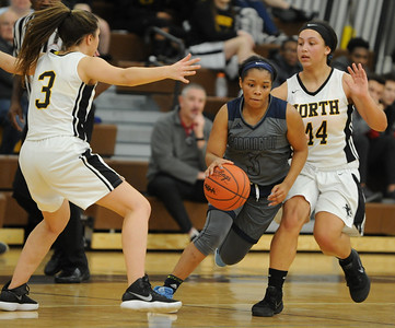 Farmington's Iasia Rimson splits the defense of North Farmington's Abby Hanus (3) and McKenna Galloway (44) during the OAA cross over game played on Wednesday January 9, 2019 at North Farmington HS.  Rimson had a team high 12 points but the Falcons lost 33-29. (Digital First Media photo by Ken Swart)