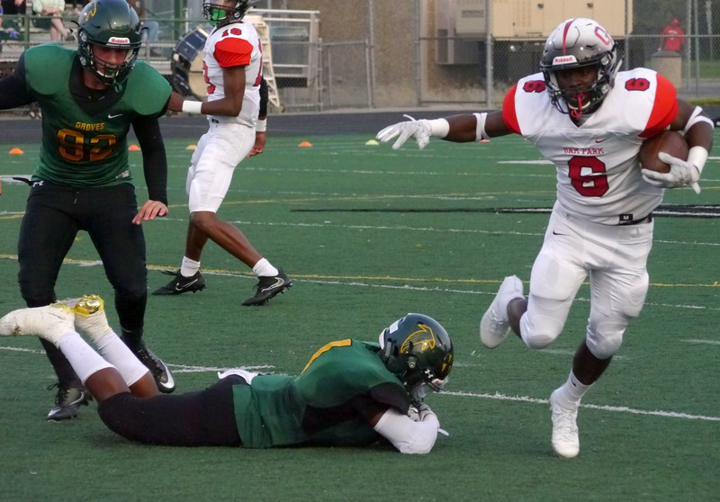 Oak Park's Torriano Richardson (6) evades a pair of Groves defenders. (Oakland Press photo gallery by Jake Thielen)