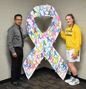 Madison Heights Bishop Foley girls basketball coach Jasper Ocampo (left) and junior Kayla Moore pose with a ribbon board, sporting individual cancer ribbons purchased during the team's Hoops for Hope night on Jan. 21, 2019. (JASON SCHMITT - For Media News Group)