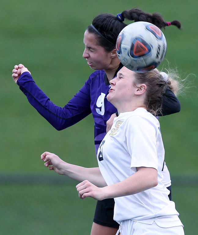 . Lauren Joneson (9), Bloomfield Hills, makes a header pass over Sarah DeGrendel, Rochester Hills Stone Creek, during varsity soccer action at Stoney Creek High School Thursday, May 3, 2018. The visiting Blackhawks tallied one goal in each half to down the Cougars 2-1. (For The Oakland Press / LARRY McKEE)