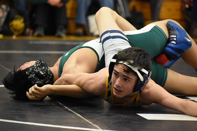 Clarkston's Dru Martin nearly pins Waterford Kettering's Seth Ly late in the second period during their 103-pound match. Martin would eventually get the pin, and help his team to a Division 1 team district title Tuesday night at Troy High School. (Digital First Media photo by Jason Schmitt)
