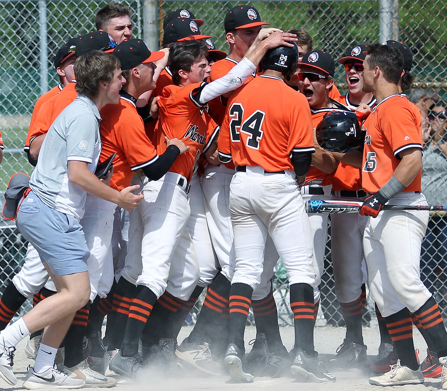 . Tito Flores (24), Birmingham Brother Rice, gets mobbed by teammates after hitting a game tying home run during district final baseball action against Birmingham Groves Saturday, June 2, 2018. Rice would go on to win the game 7-3. (For The Oakland Press / LARRY McKEE)