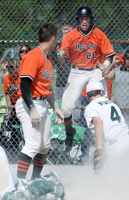 . Tito Flores (24), Birmingham Brother Rice, celebrates after teammate Jack Orlowski (foreground) scored a go ahead run during district final baseball action against Birmingham Groves Saturday, June 2, 2018. Rice would go on to win the game 7-3. Tyler Newitt (4), Groves is also pictured. (For The Oakland Press / LARRY McKEE)