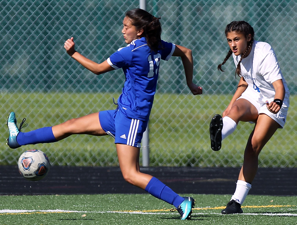 . Madison Webster (19), Madison Heights Lamphere, gets in front of a centering pass by Maria Askounis (4), Birmingham Marian, during regional semifinal soccer action at Hurley Field in Berkley Wednesday, June 6, 2018. The Mustangs dominated throughout downing Lamphere 9-1. (For The Oakland Press / LARRY McKEE)