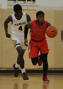 Fred Garland (1) of Oak Park moves the ball up court as North Farmington's Jamal Hayes (4) trails the play during the OAA Red match up played on Thursday February 7, 2019 at N. Farmington HS. Garland had 17 points to help lead the Knights to a 56-55 win. (Digital First Media photo by Ken Swart)