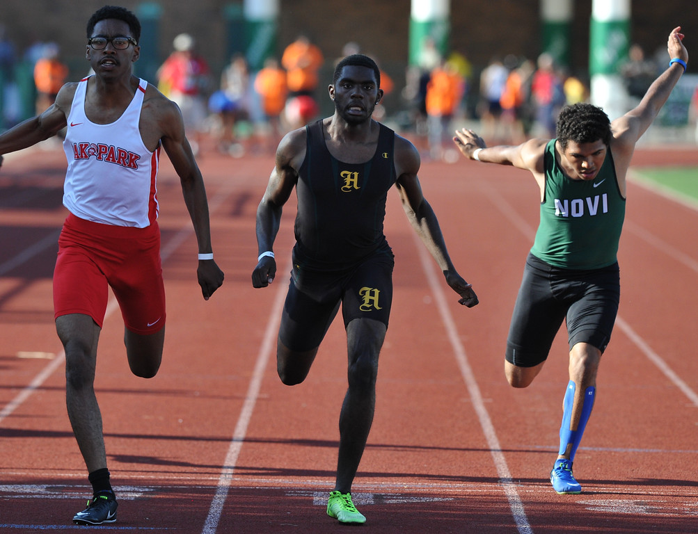 . Donnie James of Oak Park edges out FH Harrison\'s Joe Sevens and Novi\'s Sean Pitcher to win the 100M dash at the 59th annual Oakland Country Track meet held on Friday May 25, 2018 at Novi High School.  James also won the 200 and 400M events to lead the Knights to the title.  (Oakland Press photo by Ken Swart
