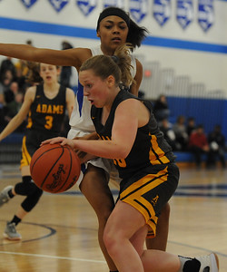 Rochester Adams' Maddie Dolenga moves around Rochester's Anna Winkler during the OAA White/Blue crossover game played on Tuesday February 5, 2019 at Rochester High School.  Dolenga had a game high 15 points to help lead the Highlanders to a 52-40 win. (Digital First Media photo by Ken Swart)