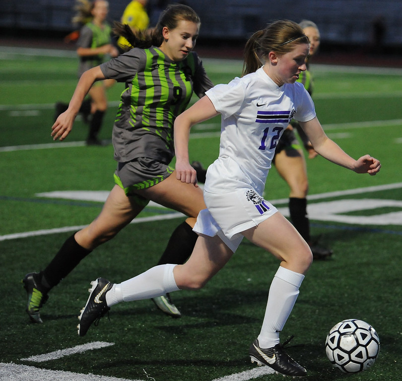 . Jenna Hart (12) of Bloomfield Hills carries the ball up field in front of Rochester\'s Sarah Novak (9) during the OAA Red match played on Thursday May 17, 2018 at Bloomfield Hills High School.  The Black Hawks lost to the Falcons 1-0.  (Oakland Press photo by Ken Swart)
