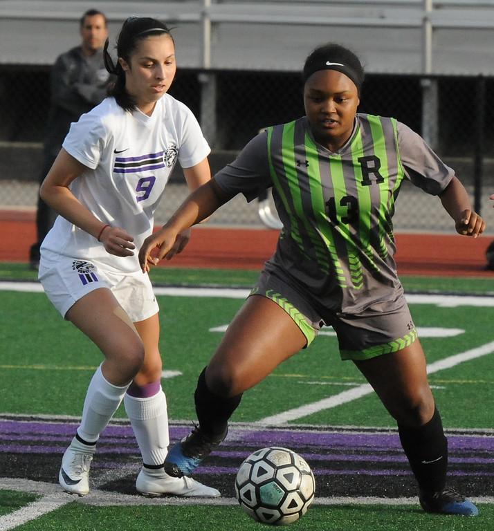 . Rochester\'s Gabby Gilmore (13) controls the ball in front of Lauren Joneson (9) of Bloomfield Hills during the OAA Red match played on Thursday May 17, 2018 at Bloomfield Hills High School.  Gilmore had the lone goal to help lead the Falcons to a 1-0 win.  (Oakland Press photo by Ken Swart)
