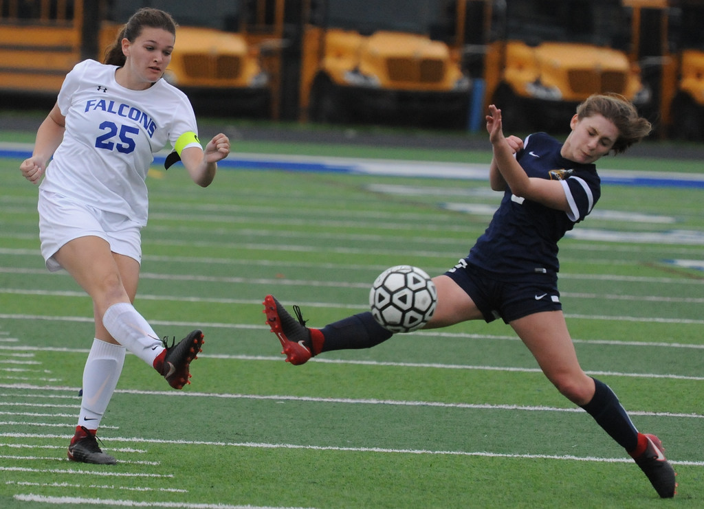 . Kiley Schneck (25) of Rochester clears the ball upfield past Talia Scicluna of Clarkston during the OAA Red matchup played on Thursday May 3, 2018 at Rochester High School.  The teams played to a 0--0 draw.  (Oakland Press photo by Ken Swart)