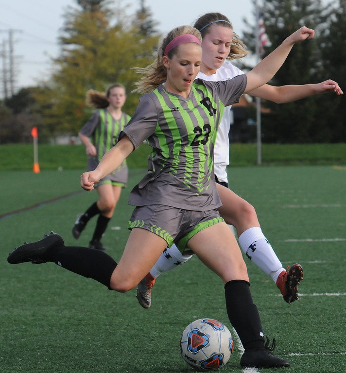 . Rochester\'s Mackenzie Smith (23) makes a cross while defended by Farmington\'s Emily Peterson during the OAA Crossover match played on Tuesday May 15, 2018 at Farmington High School.  Rochester defeated Farmington 2-0.  (Oakland Press photo by Ken Swart)