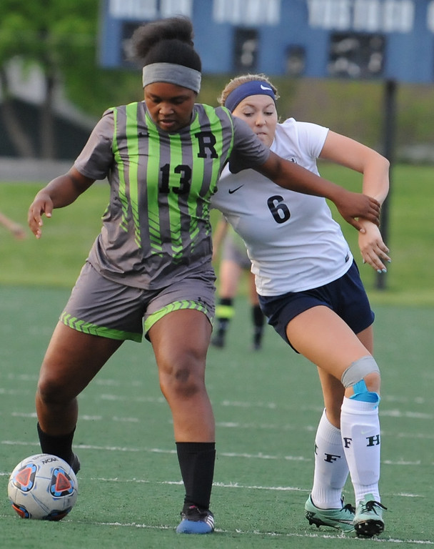 . Rochester\'s Gabby Gilmore (13) holds off Farmington\'s McKenna Greaves (6) during the OAA Crossover match played on Tuesday May 15, 2018 at Farmington High School.  Rochester defeated Farmington 2-0.  (Oakland Press photo by Ken Swart)