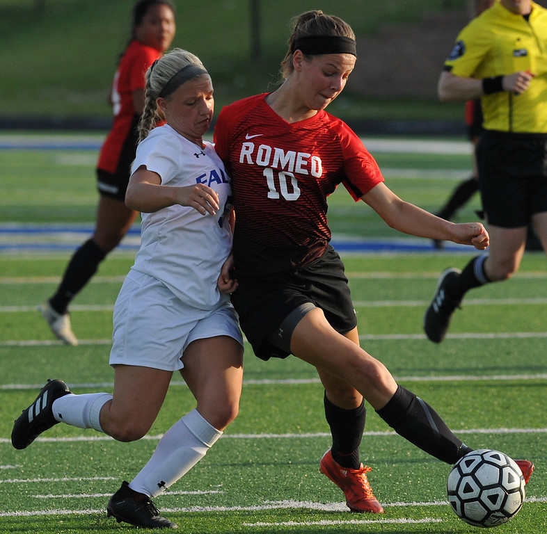 . Romeo\'s Chloe Lucci (10) controls the ball in front of Rochester\'s Mckenzie Gruzwalski during the MHSAA D1 Soccer district quarterfinal match played on Tuesday May 29, 2018 at Rochester High School.  The Falcons defeated the Bulldogs 1-0. (Digital First Media photo by  Ken Swart)