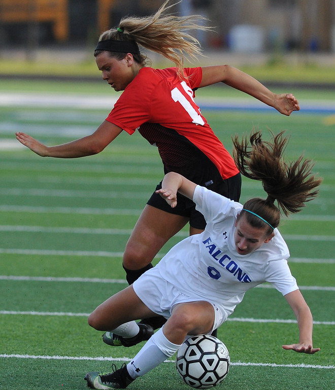 . Rochester\'s Sarah Novak (9) is upended by Romeo\'s Mya Fregoli during the MHSAA D1 Soccer district quarterfinal match played on Tuesday May 29, 2018 at Rochester High School.  The Falcons defeated the Bulldogs 1-0. (Digital First Media photo by  Ken Swart)
