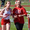 Jessica Lemond (left), who is blind, is guided along during the 4 x 800 relay reserve race with Emma Ford. Holly's boys had an easy victory but Ortonville Brandon's girls were chased to the wire in a Flint Metro League track and field meet Tuesday between the only Oakland County teams in the conference. (MIPrepZone photo gallery by MARVIN GOODWIN).