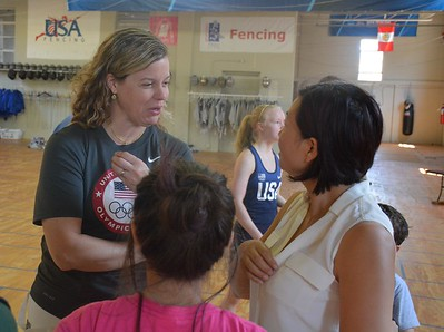 Dr. Ann Marsh-Senic chats with a parent after a fencing training session with youngsters. (Marvin Goodwin photo).