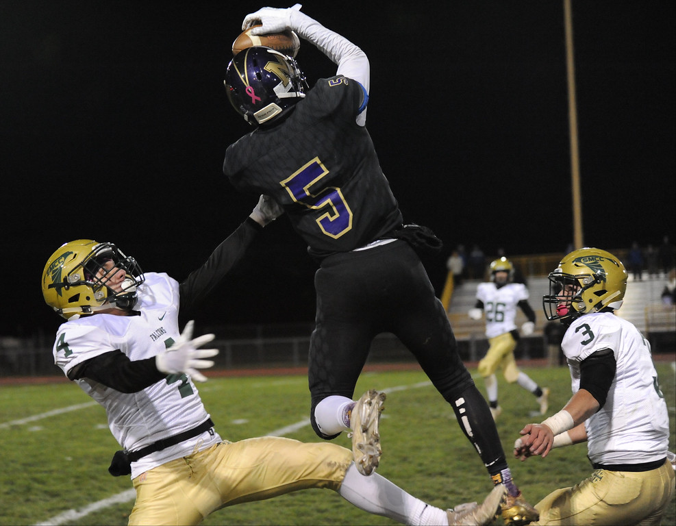 . J\'Quan Jones (5) of Madison Heights Madison makes a leaping catch between Monroe St. Mary Catholic Central\'s Mitchell Sherrard (4) and Toby Huber (3) during the MHSAA D7 Regional final played on Friday Nov. 10, 2017 at MH Madison HS.  The Eagles defeated the Falcons 22-20. (Oakland Press photo by Ken Swart)
