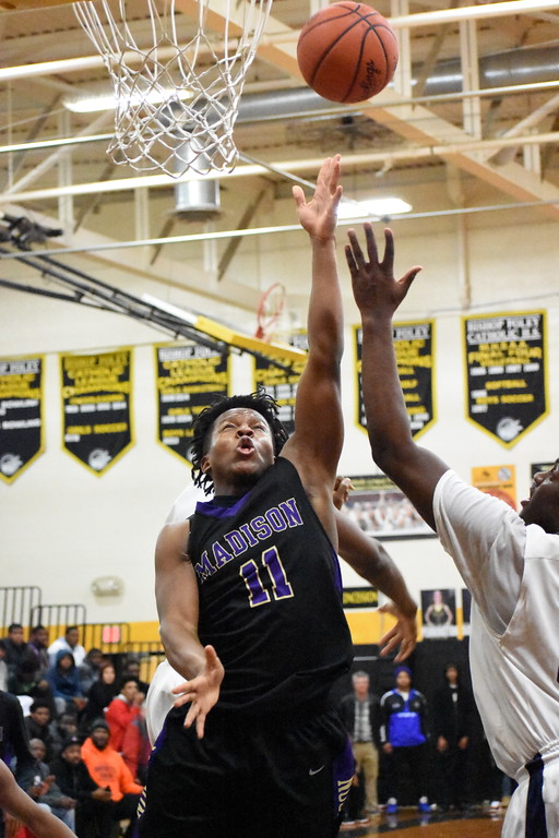 . Madison senior Demetric Knight goes up for a rebound during his team\'s 70-66 loss to Detroit Loyola Monday night in a Class C regional semifinal game at Bishop Foley High School. (Digital First Media photo by Jason Schmitt)