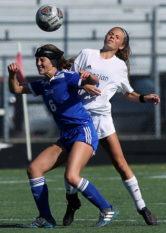 . Lauren Mexico (6), Madison Heights Lamphere, battles for ball possession at midfield with Kate Biglin, Birmingham Marian, during regional semifinal soccer action at Hurley Field in Berkley Wednesday, June 6, 2018. The Mustangs dominated throughout downing Lamphere 9-1. (For The Oakland Press / LARRY McKEE)