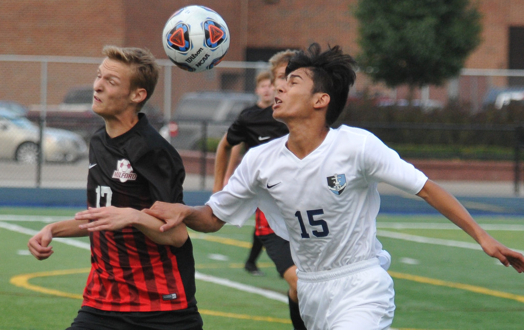 . Waterford Mott\'s Arturo Ruiz (15) and Milford\'s Michael Jacobs (17) go for a header during the match played on Monday August 21, 2017 at Waterford Mott HS.  The Corsairs lost to the Mavericks 3-2.  (Oakland Press photo by Ken Swart)