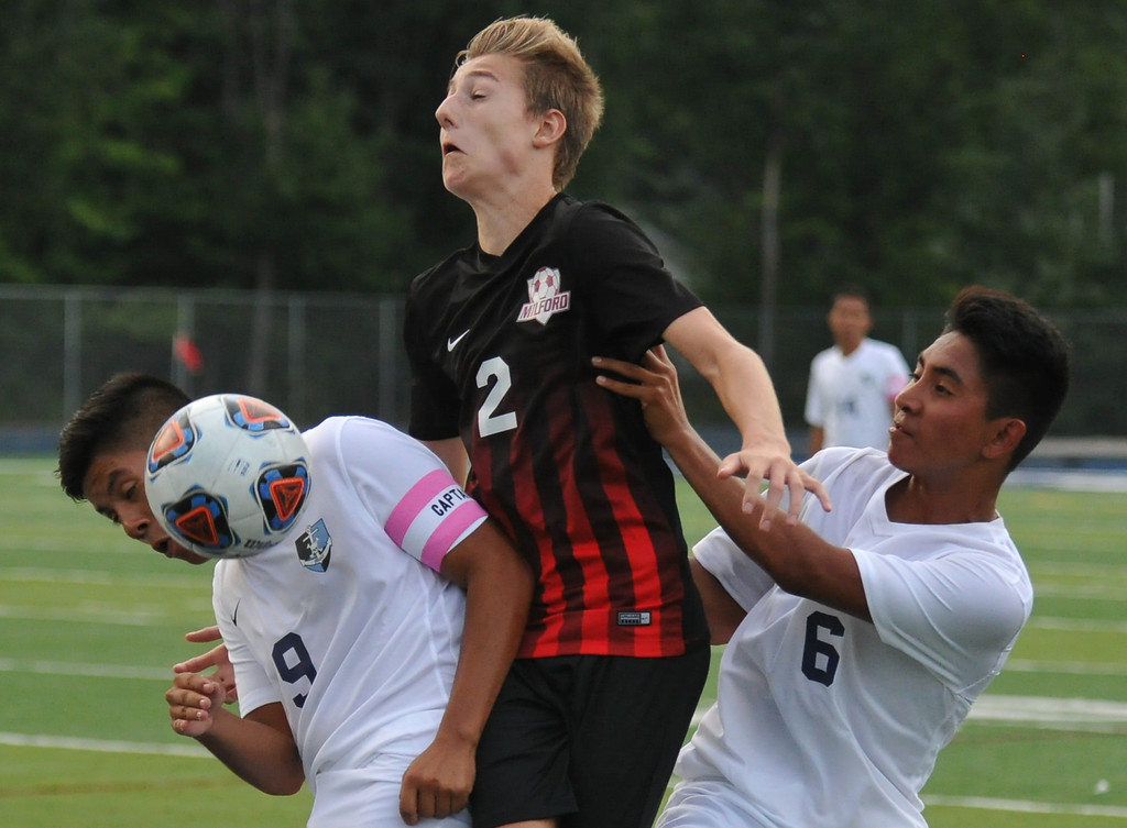 . Jack Taylor (2) of Milford tries to move between Waterford Mott\'s Steven Lopez (9) and Adrian Lopez (6) during the match played on Monday August 21, 2017 at Waterford Mott HS.  The Mavericks defeated the Corsairs 3-2.  (Oakland Press photo by Ken Swart)