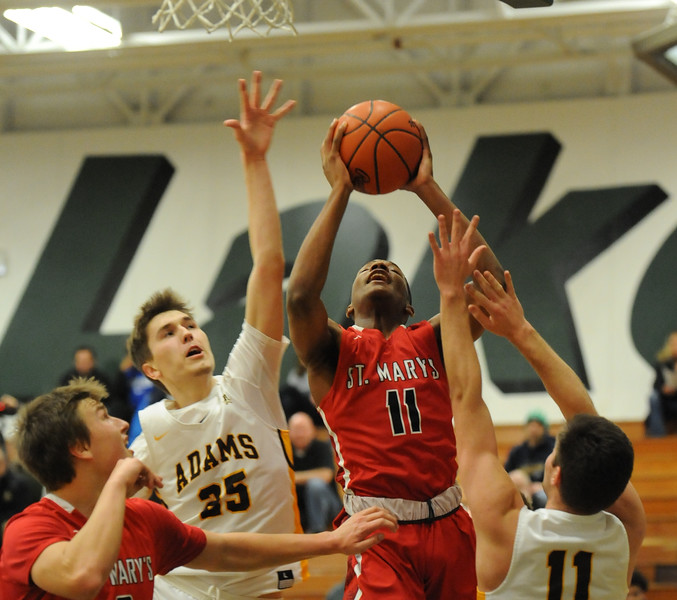 Lorne Bowman (11) of OLSM puts up two of his game high 22 points as Rochester Adams' Peyton Prieskorn (25) and Ryan Lindley (11) defend during the Class A Regional Semi-final played on Monday March 12, 2018 at West Bloomfield High School.  OLSM defeated the Highlanders 41-35.  (Oakland Press photo by Ken Swart)