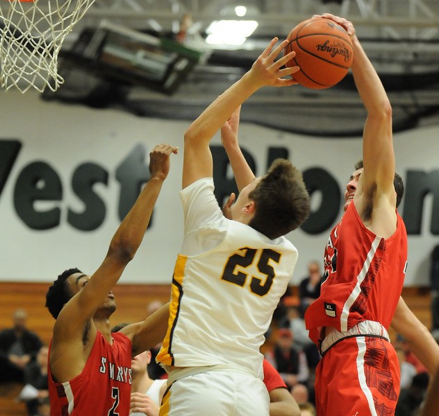 Rochester Adams' Peyton Prieskorn (25) has his shot blocked by OLSM's Nick Goerss as teammate Geordon Duncan (2) helps defend during the Class A Regional Semi-final played on Monday March 12, 2018 at West Bloomfield High School.   The Highlanders lost to the Eaglets 41-35.  (Oakland Press photo by Ken Swart)