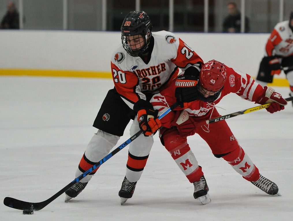 . Orchard Lake St. Mary\'s Preston Hazelton (43) delivers a body check to Brother Rice\'s Chris Andoni (20) during the game played on Wednesday December 6, 2017 at the Oak Park Ice Arena.  OLSM defeated the Warriors 5-2. (Oakland Press photo by Ken Swart)