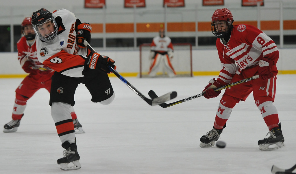 . Birmingham Brother Rice\'s Luke Kafati (9) delivers a shot as Orchard Lake St. Mary\'s Mason Moss (8) looks on during the game played on Wednesday December 6, 2017 at the Oak Park Ice Arena.  OLSM defeated the Warriors 5-2. (Oakland Press photo by Ken Swart)