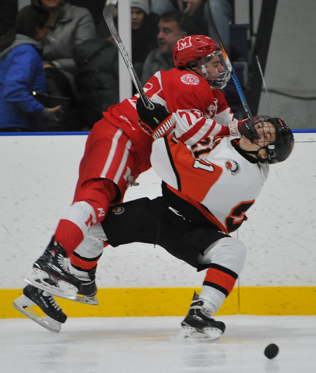 . Orchard Lake St. Mary\'s Bryce Kallen (L) upends Brother Rice\'s Anthony Potestivo (21) during the game played on Wednesday December 6, 2017 at the Oak Park Ice Arena.  OLSM defeated the Warriors 5-2. (Oakland Press photo by Ken Swart)