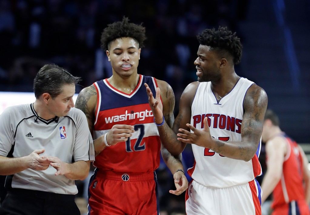 . Washington Wizards forward Kelly Oubre Jr. (12) walks between referee David Guthrie and Detroit Pistons forward Reggie Bullock (25) as Bullock argues a call during the second half of an NBA basketball game, Saturday, Jan. 21, 2017, in Auburn Hills, Mich. (AP Photo/Carlos Osorio)
