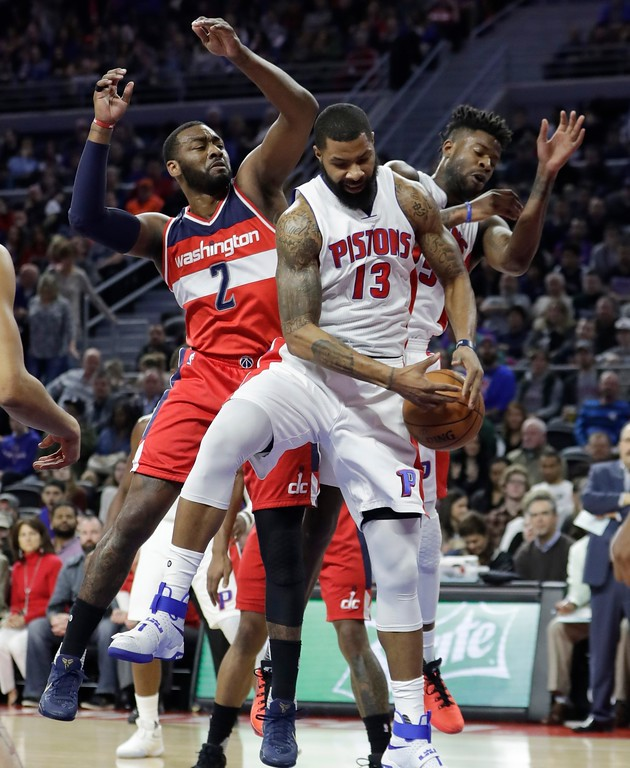 . Detroit Pistons forward Marcus Morris (13) grabs a rebound in front of Washington Wizards guard John Wall (2) during the first half of an NBA basketball game, Saturday, Jan. 21, 2017, in Auburn Hills, Mich. (AP Photo/Carlos Osorio)