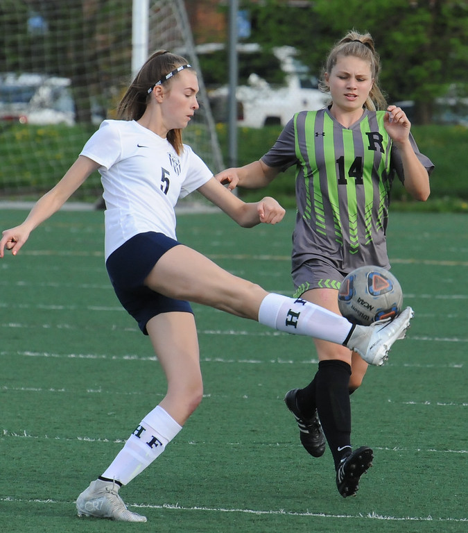 . Farmington\'s Kara Linn (5) tries to clear the ball past Rochester\'s Kaitlin DuCharme (14) during the OAA Crossover match played on Tuesday May 15, 2018 at Farmington High School.  Farmington lost to Rochester 2-0.  (Oakland Press photo by Ken Swart)